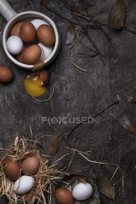 Ovos de galinha de cores brancas e marrons, um ovo rachado — Fotografia de Stock