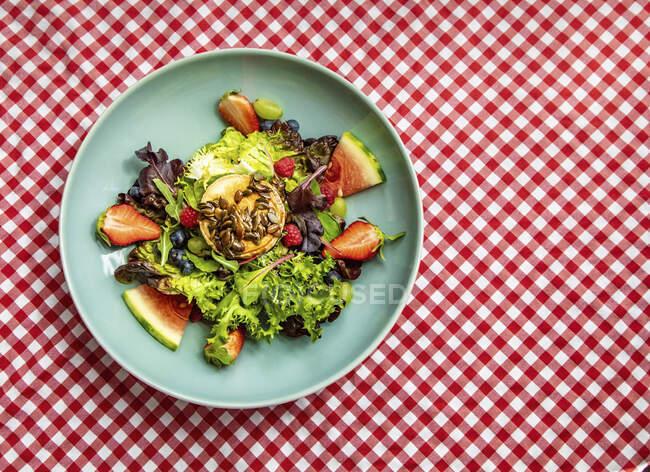 Салат з козячого роликового сиру подають з різними фруктами і свіжою зеленню. — стокове фото