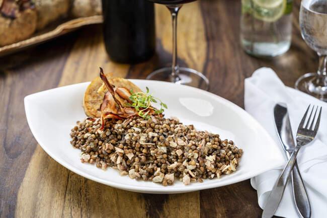 Carne a la parrilla, arroz con pollo, queso y nueces en un plato blanco sobre una mesa de madera. - foto de stock