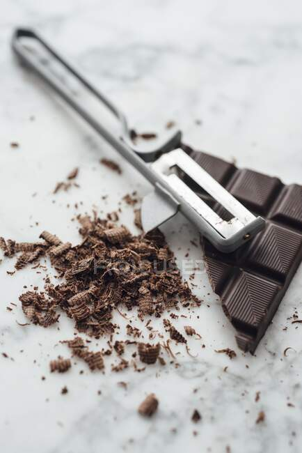 Carrés et copeaux de chocolat avec un éplucheur de légumes — Photo de stock