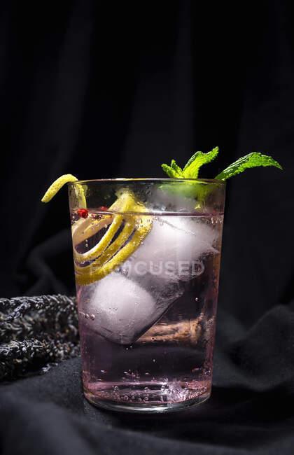 Cóctel de Gin tonic con agua tónica rosa, pimienta rosa, romero, menta, canela, limón y naranja sobre fondo oscuro - foto de stock