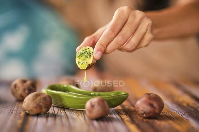 Sumergiendo deliciosa papa cocida en salsa de limón - foto de stock