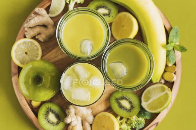 Vasos con bebidas desintoxicantes saludables con cubitos de hielo colocados en bandeja de madera con manzana y jengibre - foto de stock