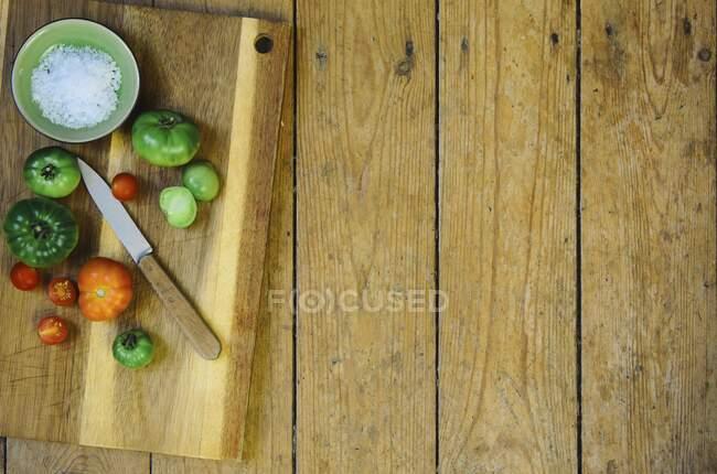 Un tazón de sal y varios tomates con un cuchillo en una tabla de cortar de madera - foto de stock