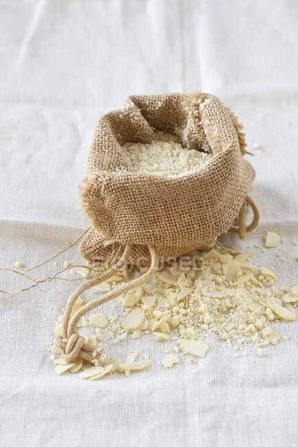 Harina de almendras en una bolsa de arpillera sobre un paño de lino - foto de stock
