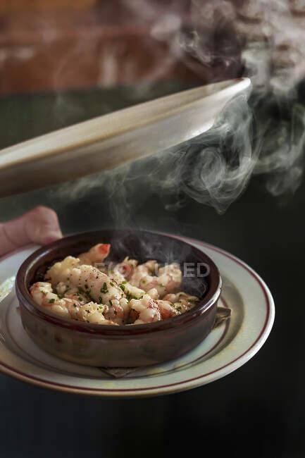 Quitar el plato del tazón de deliciosos camarones jugosos en hierbas con vapor que sale - foto de stock