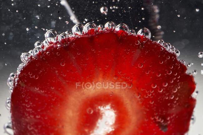 Primer plano de rodaja de fresa roja madura con burbujas de aire en agua clara - foto de stock