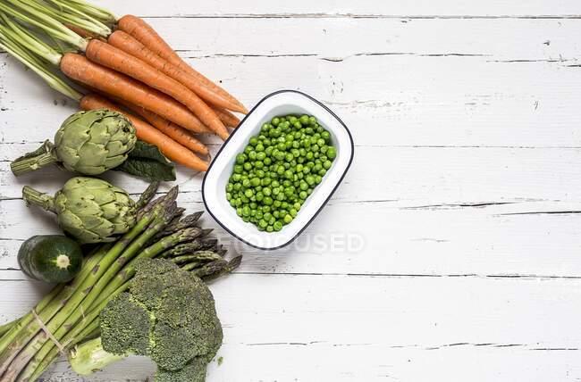 Verduras y hierbas verdes frescas sobre fondo de madera blanca. vista superior. - foto de stock