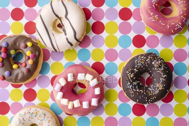 Donuts decorados de colores en un mantel punteado (vista superior) - foto de stock