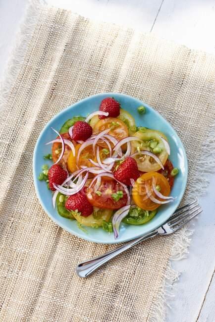 Томатний салат з цибулею, полуницею і виделкою. — стокове фото