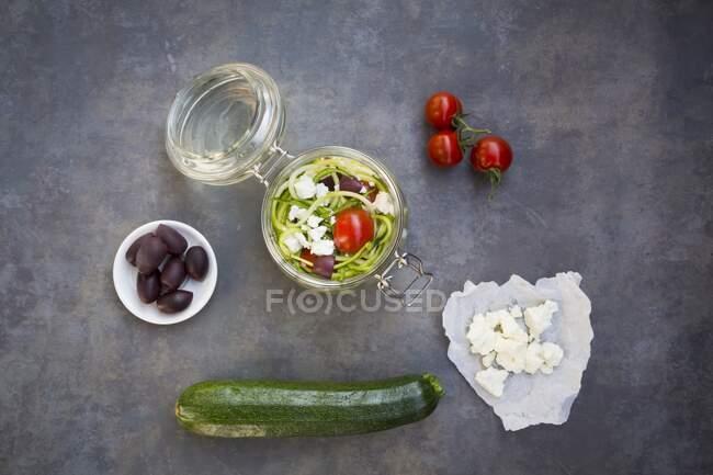 Fideos de calabacín en frasco de vidrio con tomates, feta y aceitunas - foto de stock