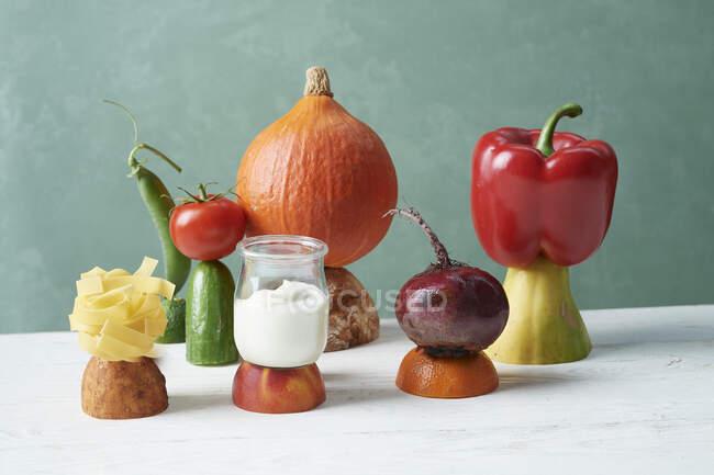 Un arreglo de frutas, verduras, yogur y pasta - foto de stock
