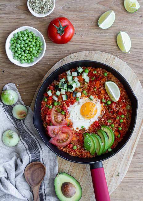 Shakshuka con huevos y quinua puestos en la mesa con ingredientes frescos - foto de stock