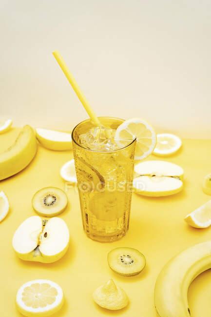 Várias frutas frescas dispostas em fundo amarelo com copo de coquetel com palha e gelo — Fotografia de Stock