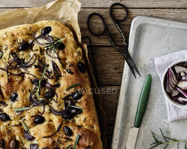 Focaccia con aceitunas negras y hierbas sobre mesa de madera - foto de stock