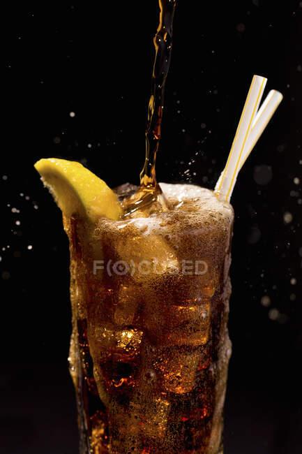 Склянка коли на чорному тлі з великою зливою, переповнена бульбашки, бризки, соломи і лимон. — стокове фото