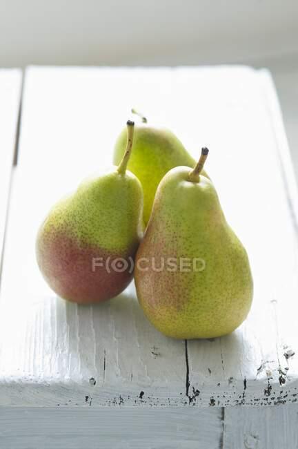 Tres peras verdes sobre un fondo de madera blanco - foto de stock