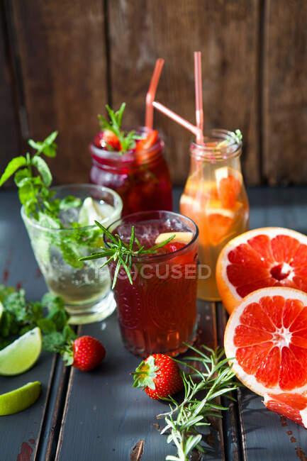 Vários copos de coquetéis frutados, jarra e garrafa — Fotografia de Stock