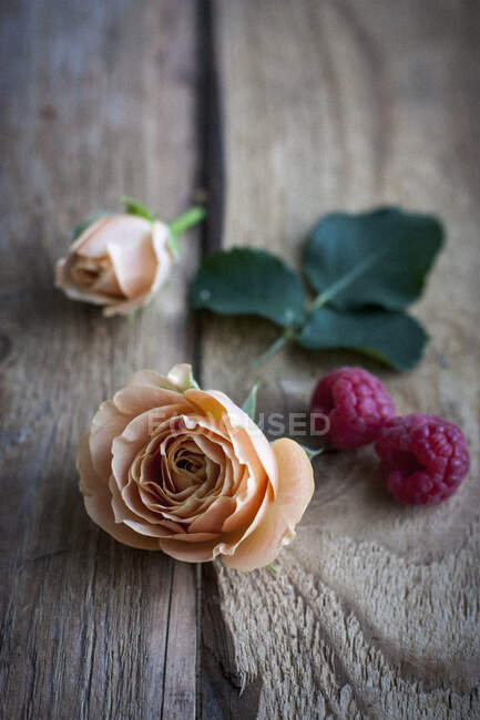 Розы и малина на деревенской деревянной поверхности — стоковое фото