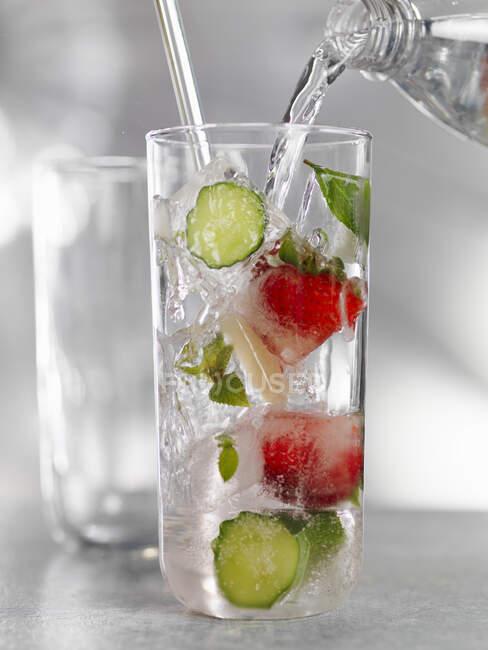 Água que despeja da garrafa em vidro com pepino e morangos — Fotografia de Stock