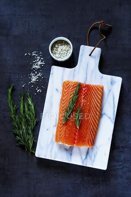 Filete de salmón fresco crudo con romero y sal gris sobre tabla de cortar marbre - foto de stock