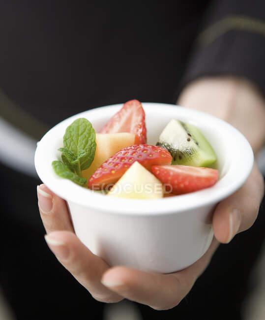 Mão segurando uma pequena bola branca com salada de frutas mistas — Fotografia de Stock