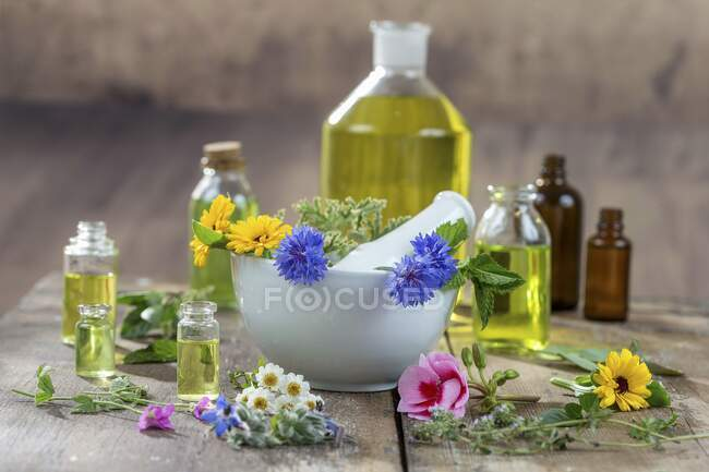 Various healing flowers, herbs and oils in and around a mortar — Stock Photo