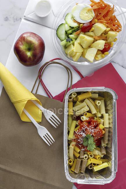 Hortalizas con huevo cocido y macarrones con ketchup y queso para llevar - foto de stock