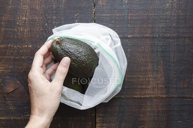 Persona que toma aguacate del saco - foto de stock