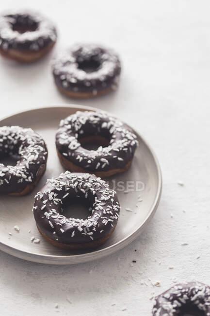 Donuts con glaseado de chocolate y trozos de coco - foto de stock