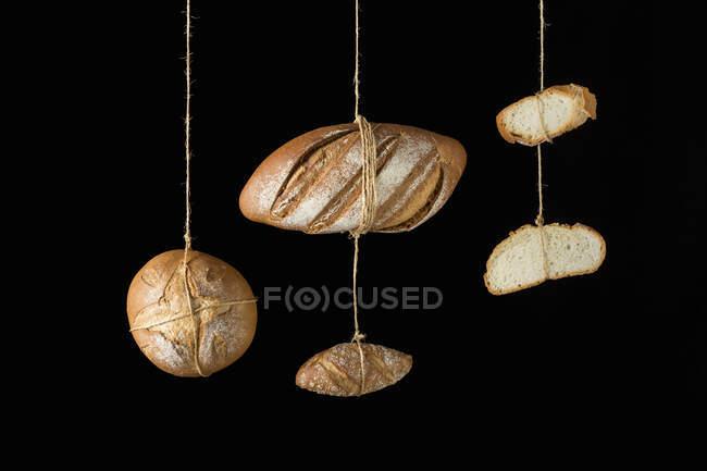 Лоферы и куски ремесленного хлеба, висящие на веревках — стоковое фото