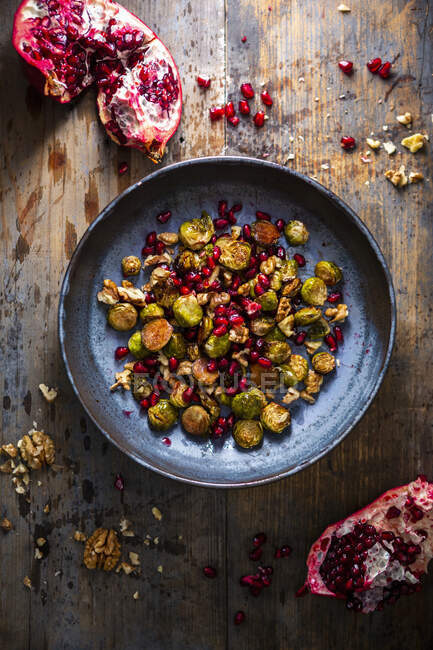 Ensalada de coles de Bruselas con semillas de granada y nueces - foto de stock