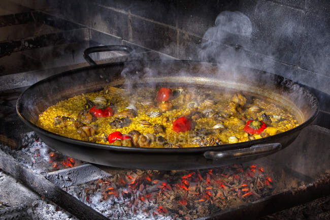 Hot delicious paella with rice, chicken and vegetables cooked in iron pan over open fire — Stock Photo