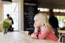Девушка смотрит в сторону, сидя — стоковое фото