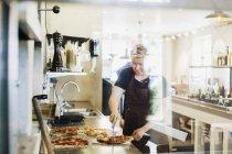 Köchin schneidet Pizza — Stockfoto