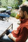 Man drinking coffee on table at greenhouse — Stock Photo
