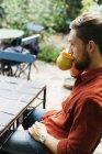 Uomo che beve caffè sul tavolo al serra — Foto stock