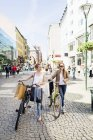Women with bicycles on street — Stock Photo