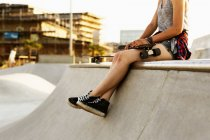 Teenager-Mädchen mit Skateboard sitzt am Rand — Stockfoto