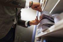 Vendedor clerk remoção camisa da prateleira — Fotografia de Stock