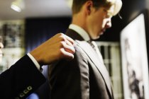 Sales clerk adjusting customers suit — Stock Photo