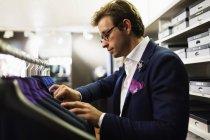 Vendeur, analysant les costumes — Photo de stock