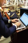 Vendedor usando el ordenador portátil - foto de stock