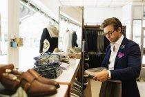 Sales clerk looking at t-shirt — Stock Photo