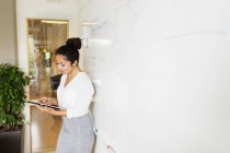 Businesswoman standing and using digital tablet — Stock Photo