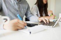Businessman writing and using laptop — Stock Photo