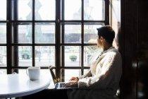 Freelancer mirando por la ventana - foto de stock