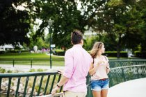 Friends standing on footbridge in park — Stock Photo