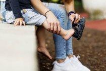 Мать помощь сына в носить сандалии — стоковое фото
