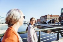 Businesswoman looking at colleague while walking on bridge — Stock Photo